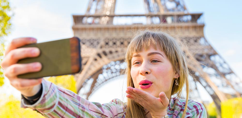 woman with cellphone in fvrom of the Eiffel Tower